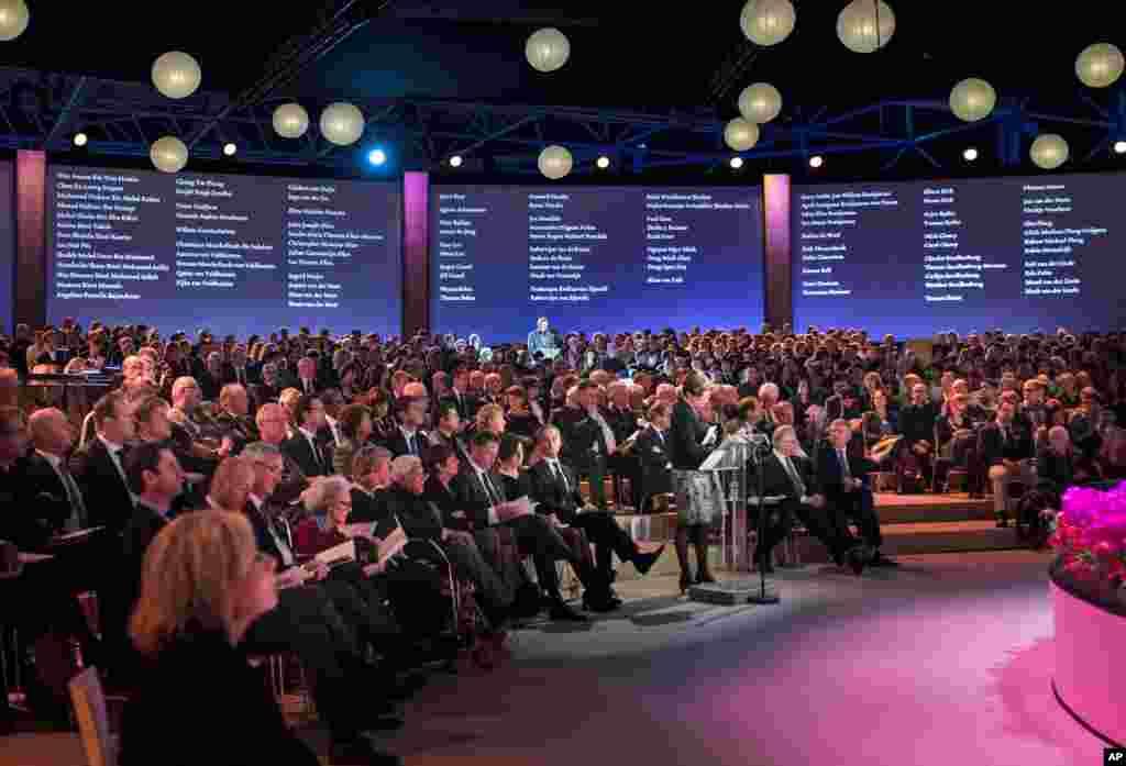 Seorang kerabat membacakan daftar nama-nama korban yang diproyeksikan ke sebuah layar dalam upacara peringatan bagi para kerabat dan kawan korban bencana Malaysia Airlines penerbangan 17, di Amsterdam (10/11).(AP/Frank van Beek)
