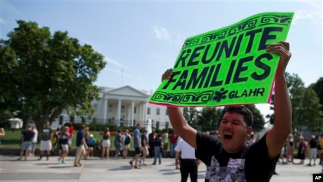 FILE - Carlos Guzman of Albany, Ga., holds a sign during an immigration reform rally in front of the White House, Washington, July 24, 2013.