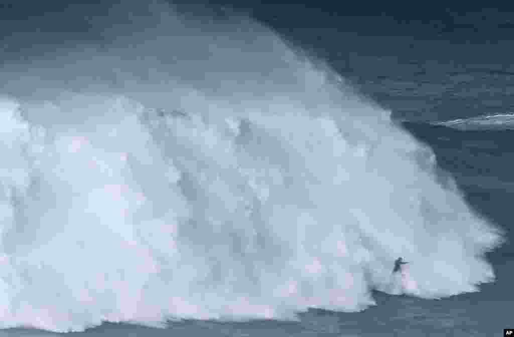 Peselancar putri Brazil Maya Gabeira melawan ombak besar di pantai Praia do Norte, di Nazare, Portugal.