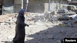 Người đàn bà rời khu phố đổ nát sau khi trở về để nhìn ngôi nhà bị hư hại của bà trong quận Bustan al-Basha của Aleppo