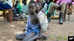一名南蘇丹小男孩坐在地上看著樂施會分發救援物資。 (2018年8月17日)