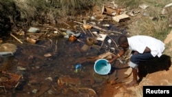 Residences of Mabvuku fetch water from unproteacted sources in Harare, Zimbabwe, July 28, 2012.