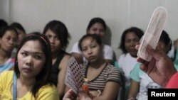FILE - A community health worker holds up contraceptives during a lecture on family planning at a reproductive health clinic run by an NGO in Tondo city, metro Manila, Jan. 12, 2016.