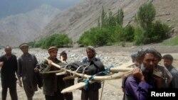Warga membawa korban banjir di distrik Gozargah-e Noor provinsi Baghlan 7 Juni 2014.