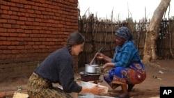 Cameron Beach, left, sieves maize flour as she helps prepare a meal, in Dedza, near Lilongwe, Malawi, July 23, 2021.
