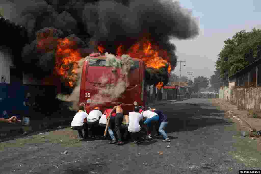 Demonstrators push a bus that was torched during clashes with the Bolivarian National Guard in Urena, Venezuela, near the border with Colombia, Feb. 23, 2019. Venezuela's National Guard fired tear gas on residents clearing a barricaded border bridge between Venezuela and Colombia, heightening tensions over blocked humanitarian aid that opposition leader Juan Guaido has vowed to bring into the country over objections from President Nicolas Maduro.