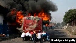 Демонстранти штовхають підпалений під час сутичок з Національною гвардією Венесуели автобус в Урені, Венесуела, біля кордону з Колубмією. 23 лютого 2019 року.