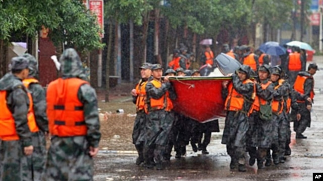Chinese rescuers carry their boats in to evacuate residents in Fuzhou, Jiangxi province, 24 Jun 2010