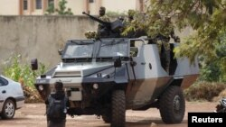 FILE - Presidential guard soldiers are seen on an armored vehicle at Laico hotel in Ouagadougou, Burkina Faso, Sept. 20, 2015.