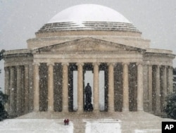 Visitors to the Jefferson Memorial in Washington, walk down the front steps on a snowy Presidents Day moliday in the Nation's Capital, Feb. 15, 2016.