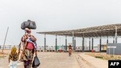 Des voyageurs marchent pour traverser la frontière Togo-Bénin située à Hillacondji le 29 avril 2021.