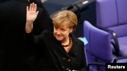 German Chancellor Angela Merkel waves as she makes her way to cast her vote for re-election as Chancellor during a meeting at the Bundestag, the lower house of parliament, in Berlin, Dec. 17, 2013
