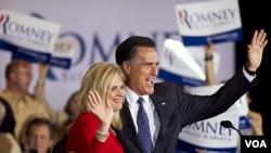 Mitt Romney dan isterinya merayakan kemenangan di Illinois (20/3). Meskipun memimpin kontes, Romney masih harus terus berjuang.