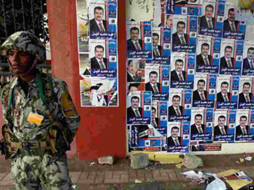 An Egyptian soldier stands next to posters of parliamentary candidates outside a polling center in Assuit, south of Cairo.