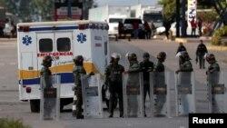 Xe cứu thương chở những người dân bản địa bị thương chạy ngang qua các binh sĩ vệ binh quốc gia của Venezuela trên đường trở vềVenezuela, tại biên giới giữa Venezuela và Brazil, ở Pacaraima, bang Roraima, Brazil, ngày 22 tháng 2, 2019.
