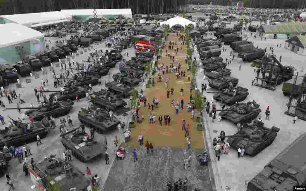 Visitors walk near exhibits, which are on display at the Army-2015 international military-technical forum in Kubinka, outside Moscow, Russia.