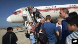 旅客在平壤国际机场登上前往北京的飞机