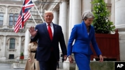 Britain's Prime Minister Theresa May and President Donald Trump walk through the Quadrangle of the Foreign Office for a joint press conference in central London, June 4, 2019.