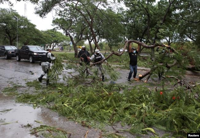 Anggota Garda Nasional menyingkirkan dahan pohon dari jalan setelah Badai Grace mendarat di Semenanjung Yucatan, di Merida, Meksiko, 19 Agustus 2021. (Foto: Reuters)