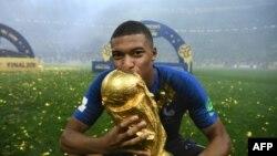 L'attaquant des Bleus, Kylian Mbappé embrasse la Coupe du Monde à Moscou, le 15 juillet 2018