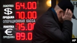 FILE - In this Dec. 16, 2014 file photo, a man walks by a sign advertising currencies of an exchange office in Moscow, Russia.
