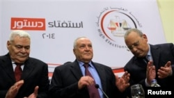 Judge Nabil Salib, head of Egypt's High Election Commission, center, is greeted by fellow commissioners as he prepares to announce voting results of referendum on military-backed constitution, Cairo, Jan. 18, 2014.