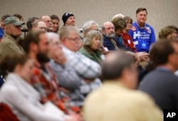 FILE - John Grause, top right, precinct captain for Democratic presidential candidate Hillary Clinton, sits with voters during a Democratic party caucus in Nevada, Iowa, Feb. 1, 2016.