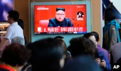 "FILE - People watch a TV screen showing an image of North Korean leader Kim Jong Un during a news program at the Seoul Railway Station in Seoul, South Korea, April 21, 2018. The signs read: ""North Korea says it has suspended nuclear tests."""