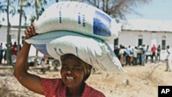 A woman looks happy after receiving bags of food