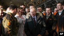 Russian President Vladimir Putin listens to employees of Uralvagonzavod factory in Nizhny Tagil, Russia, March 6, 2018.