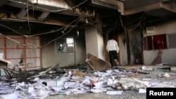 2013年9月26日在喀土穆﹐一名男子走過一間因為抗議燃料補貼削減而受到破壞的銀行