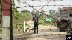 FILE - A Myanmar police officer stands watch as journalists arrive in the village of Shwe Zar, in the northern part of Myanmar's Rakhine state, Sept. 6, 2017.