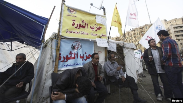 "Protesters against Egypt's President Mohamed Morsi rest in front of a tent named ""Revolution Party"" at Tahrir Square in Cairo, December 17, 2012."