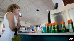 U.S. Congresswoman Debbie Wasserman Schultz, sips Cuban coffee next to a counter with cans of insect repellent. She held a news conference at David's Cafe Cafecito, Monday, Aug. 22, 2016, in Miami Beach, Florida and called for more federal help to fight Zika. (AP Photo/Wilfredo Lee)