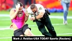 Un supporter qui a couru sur le terrain pendant le match est plaqué par un agent de sécurité durant le Super Bowl entre Kansas City Chiefs et Tampa Bay Buccaneers au stade Raymond James, en Floride, le 7 février 2021.