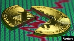 FILE - Illustration of the Bitcoin virtual currency, placed on a monitor that displays stock graph and binary codes, are seen in this illustration picture, Dec. 21, 2017.