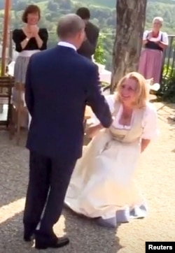 Austria's Foreign Minister Karin Kneissl dances with Russia's President Vladimir Putin at her wedding in Gamlitz, Austria, Aug. 18, 2018, in this picture grab taken from video. Kneissl's critics saw her curtsy to Putin as a sign of submission.