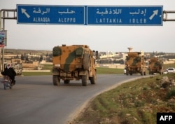 Turkish military vehicles drive in a convoy headed for the south of Idlib province as they pass the town of Atareb in the western countryside of Aleppo province, Feb. 3, 2020.