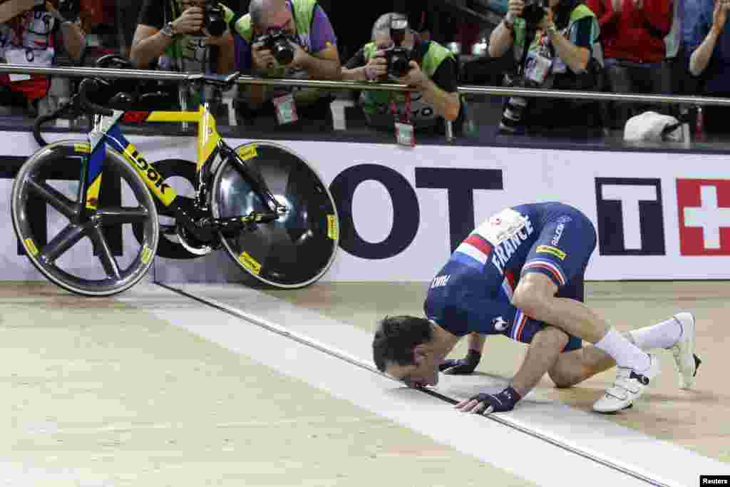 Morgan Kneisky of France kisses the finish line after his victory with teammate Bryan Coquard in the Men's Madison final at the UCI Track Cycling World Cup in Saint-Quentin-en-Yvelines, near Paris, France.