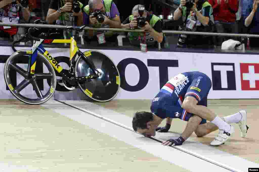 Morgan Kneisky, Perancis, mencium garis finish setelah menang bersama rekan satu timnya Bryan Coquard di final putra Madison di UCI Track Cycling World Cup di Saint-Quentin-en-Yvelines, dekat Paris, Perancis.