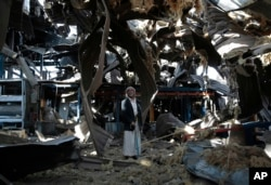 FILE - An elderly man stands among the rubble of the Alsonidar Group's water pump and pipe factory after it was hit by Saudi-led airstrikes in Sana'a, Yemen, Sept. 22, 2016.