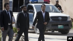 Zakarya Ahmad Al-Fattah (R), brother of Osama bin Laden's youngest widow, Yemen-born Amal Al-Sadeh, arrives with their lawyer Amir Khalil (L) to attend court proceedings at a house where bin Laden's family is believed to be detained in Islamabad April 2,