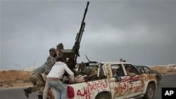 Libyan rebels jump onto back of their vehicle as they leave Ras Lanouf in central Libya after Gadhafi's forces drove rebels out of Bin Jawwad, a hamlet east of Sirte, March 29, 2011