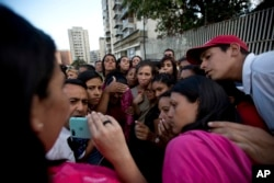Relatives of prisoners watch in a mobile phone a video released by the prisoners outside of Venezuelan political police headquarters, SEBIN, in Caracas, Venezuela, Wednesday, May 16, 2018.
