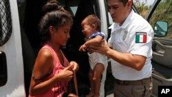 Un agente de inmigración de México sostiene al bebé de una mujer bajo su custodia para que ella coloque su maleta el lunes 22 de abril de 2019.