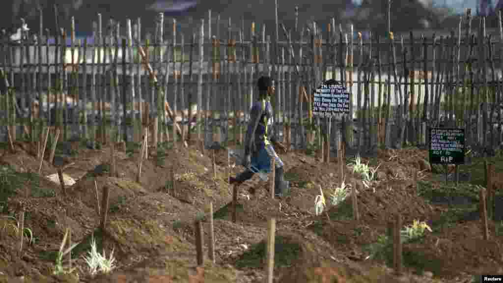 Un fossoyeur marche à travers les fosses nouvellement creusées pour l'enterrement des victimes d'Ebola dans un cimetière de Freetown, 4 décembre 2014. REUTERS / Baz Ratner
