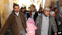 Residents of the Tizimi neighborhood in Meknes' old quarter carry from the morgue a victim of the collapse of a historic minaret, February 20, 2010