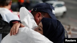 A Syrian migrant embraces a rescuer before disembarking from the Malta-based NGO Migrant Offshore Aid Station (MOAS) ship Phoenix after it arrived with migrants and a corpse, in Catania on the island of Sicily, Italy, May 6, 2017.