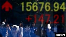 Sebuah papan elektronik di Tokyo menunjukkan naiknya harga saham Dow Jones, 19 September 2013. Indeks Niikei Jepang dilaporkan juga mencapai angka tertinggi dalam delapan bulan terakhir, naik hampir dua persen. (REUTERS/Toru Hanai)