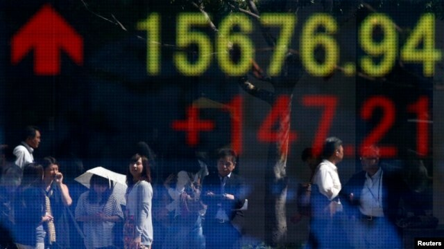People are reflected in an electronic board outside a Tokyo brokerage,  Sept. 19, 2013.